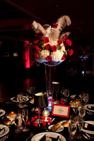The low centerpieces featured red roses white hydrangea and black ostrich